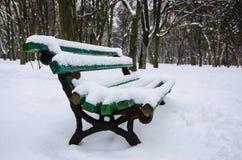 长凳在雪下的公园 库存图片