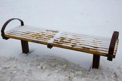 长凳在雪下的公园 库存照片
