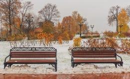 长凳在雪下的秋天公园 免版税库存照片