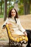 长凳坐的smilling的妇女年轻人 库存图片