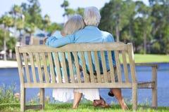 长凳夫妇停放后方高级坐的视图 免版税库存图片