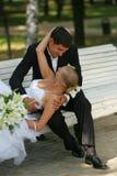长凳新娘新郎亲吻的公园 免版税库存图片
