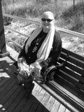 长凳更老的微笑的妇女 库存图片
