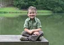长凳男孩交叉有腿的池塘 免版税库存照片