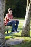 长凳男孩坐的微笑少年 免版税库存照片