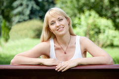 长凳白肤金发的快乐的夏天妇女年轻&# 库存图片