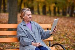 长凳的一名成熟妇女在她的手上拿着一种片剂并且调查它 在秋天的公园 免版税库存照片