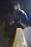 长凳的冰球球员 免版税库存图片