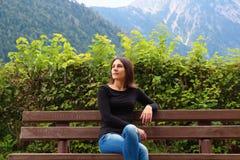 长凳的女孩在阿尔卑斯背景  免版税库存图片