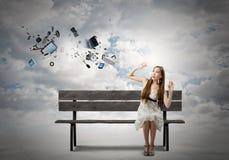 长凳的女孩 免版税库存照片