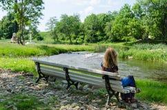 长凳的妇女敬佩快速的流程河水小河 免版税库存图片