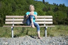 长凳的妇女 图库摄影