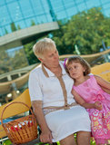 长凳的小女孩与祖母 免版税库存图片