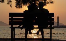 长凳的爱恋的人在剪影 库存图片