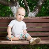 长凳的男孩 图库摄影