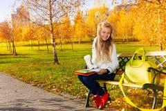 长凳的白肤金发的学校女孩在公园 免版税库存图片