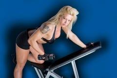 长凳的美丽的女孩在健身中心 免版税库存图片