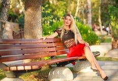 长凳的美丽的梦想的妇女在城市公园在夏天 库存照片