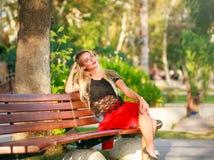 长凳的美丽的梦想的妇女在城市公园在夏天 免版税图库摄影