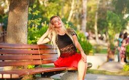 长凳的美丽的梦想的妇女在城市公园在夏天 库存图片