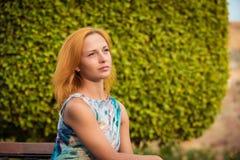长凳的年轻红色妇女 免版税图库摄影