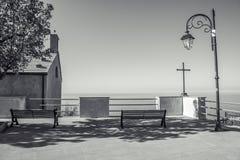 长凳,简单的教会和十字架lookin在地中海 库存照片