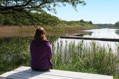 长凳ovelooking的湖的妇女 库存照片