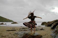长发夫人剧烈的画象花卉正装的在与开放的胳膊的一个风雨如磐的海滩 免版税库存图片