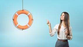 长发女实业家指向垂悬从绳索的一个小橙色救生圈 免版税库存照片
