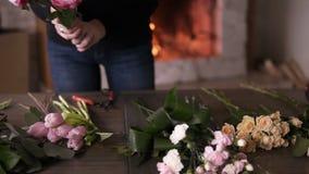 长发深色的卖花人花为她的未来花束做准备 安排在桌上的不同的花-郁金香 股票录像
