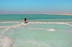 长发深色的妇女坐盐 在以色列浇灌死海表面有山约旦看法  合并本质 免版税图库摄影