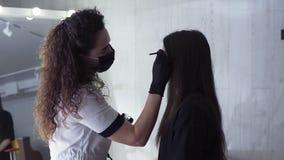 长发白种人美容师由棕色染料应用在年轻女人的眉头的黑暗的油漆,上色在a的做法 影视素材