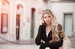长发白肤金发的女孩在街道上的电话里说 G 库存图片