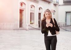 长发白肤金发的女孩在街道上的电话里说 G 免版税库存图片
