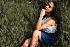 长发青少年的女孩坐草草甸 免版税库存照片