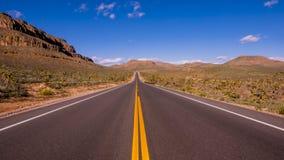 长和空的幽静路通过亚利桑那 免版税库存照片