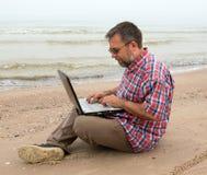 年长商人与笔记本坐海滩 免版税库存图片