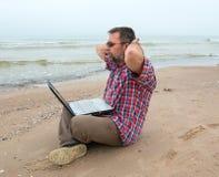 年长商人与笔记本坐海滩 免版税库存照片
