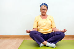 年长在健身房的女子实践的瑜伽 图库摄影