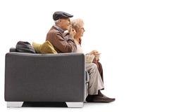 年长坐沙发和吃玉米花的男人和妇女 免版税库存图片
