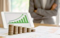 长大与事务的硬币堆并且提供经费给图表屏幕 免版税库存照片