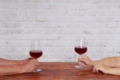年长夫妇在测试红葡萄酒的餐馆 免版税图库摄影
