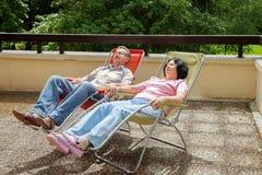 年长夫妇在晴朗的大阳台的休息室放松 库存照片
