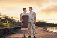 年长夫妇走的谈话嘲笑日落在湖河附近 免版税库存照片