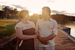 年长夫妇走的谈话嘲笑日落在湖河附近 免版税库存图片