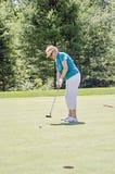 年长女子打高尔夫球 库存图片