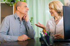 年长女性医生谈话与年迈的男性患者 库存图片