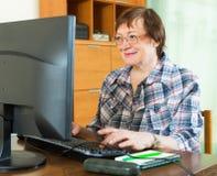年长妇女与计算机一起使用 免版税库存图片