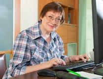 年长妇女与计算机一起使用 免版税图库摄影