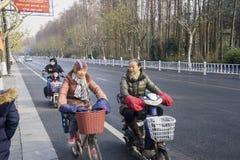 年长妇女乘驾自行车在杭州 库存照片